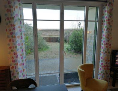 L'accès au jardin se fait par une grande baie vitrée.