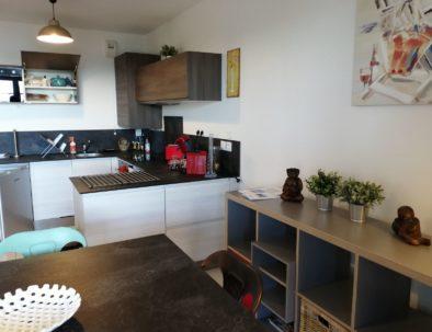 Le coin repas est juste à côté de le cuisine intégrée, dont le meuble à vaisselle est tourné vers le coin repas.